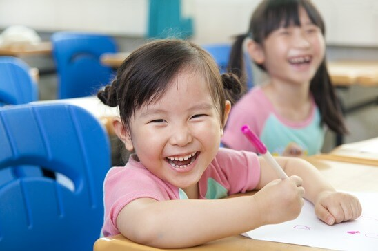 Little girl smiling while drawing - Home Tuition Hotspot Singapore