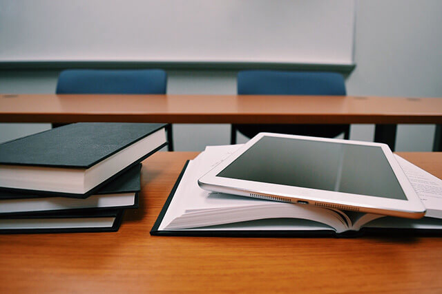 Pile of books on top of a table with an open book and tablet - Home Tuition Hotspot Singapore
